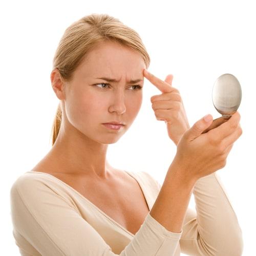 Frau sieht Akne im Spiegel