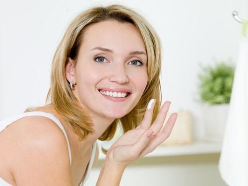 Blonde Frau mit kurzen Haaren, lächelt und hat Creme auf ihrem Finger.