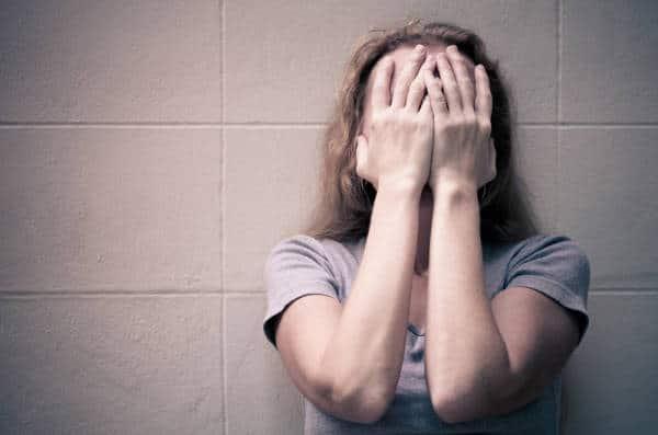 Frau hält sich verzweifelt ihre Hände vor das Gesicht