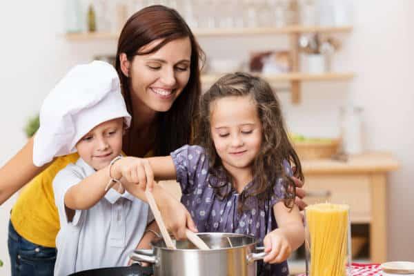 Mutter mit Kindern beim Kochen
